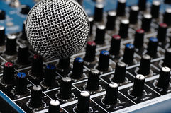 Audio mixer and a silver microphone. Sound console with buttons in the background and a dynamic microphone in the foreground stock image