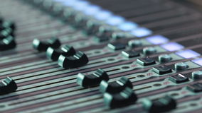 Audio mixer in a studio, the automatic knobs moving up on console. Close-up DOF stock footage
