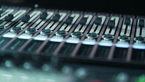 Audio mixer in a studio, the automatic knobs moving up on console. Close-up DOF stock video footage
