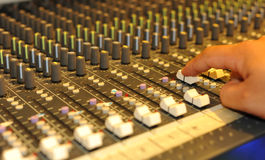 Audio mixing board. Close-up of sound engineer's hand moving sliders on audio mixing board Stock Images