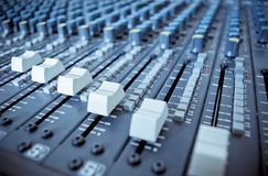 Audio Mixing Board Sliders. Close up image of an audio mixing board with several channels and push buttons visible. Dials and volume levels are also visible royalty free stock image