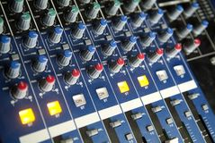 Audio Mixing Console. An array of rotary controls, sliders, and bottons on audio mixing console Royalty Free Stock Photo