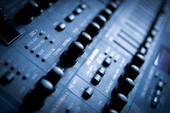 Audio mixing console. Toned in blue with close up of the knobs stock images