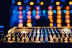 Audio mixing control panel. Or keybord with buttons against background with de focused concert spotlights royalty free stock photos