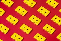 Audio nastri a cassetta gialli su fondo rosso Concetto creativo di retro tecnologia Fotografie Stock