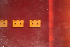 Audio nastri a cassetta gialli su fondo rosso, sulla vista superiore tonificata e sui graffi Concetto creativo di retro tecnologi Immagine Stock