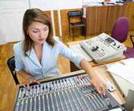 Audio operator at audio control console. Female audio operator at sound mixing console royalty free stock photography