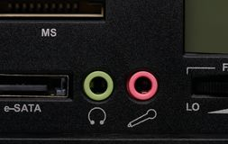 Audio output/input sockets. Audio headphone output socket and audio microphone input socket on the black panel, closeup shot Royalty Free Stock Photo