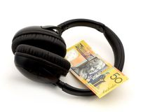 Audio purchase. Headphones with 50 australian dollar note over white Stock Images