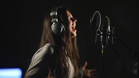 Audio recording studio. Woman with headphones and studio microphone singing. Stock Photo