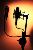 Audio recording vocal studio voice microphone. Silhouette with anti shock mount and built in anti pop filter for singing and voiceover actors doing voiceovers Stock Photography