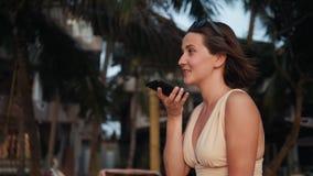Audio riconoscimento della voce di ai del messaggio su discorso mani libere dello smartphone giovane bella donna felice con il te video d archivio