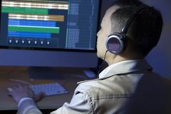 Audio sound editor. Asian male amateur sound editor edits and cuts sound audio on a computer, wears headphones monitor Royalty Free Stock Image