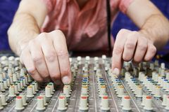 Audio sound mixing. Close-up hands of sound engineer work with faders and knobs on professional audio musical mixer Stock Photos