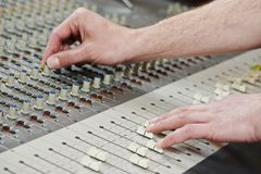 Audio sound mixing. Close-up hands of sound engineer work with faders on mixer Royalty Free Stock Photos