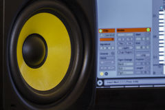 Music Production. Close Up of an Audio Speaker with music production software in the background Stock Images