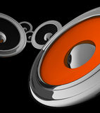 Audio speakers. 3D concept of black, orange audio speakers in metal cases, isolated on black Royalty Free Stock Images