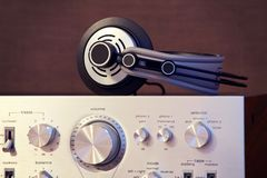 Audio Stereo Headphones on the top of Vintage Amplifier. Front View royalty free stock image