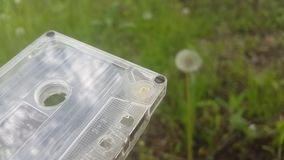Audio tape on a background of dandelion and grass.  stock footage