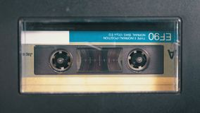 Audio Tape. Vintage Tape Recorder Plays Audio Cassette inserted therein. Macro static camera view of retro audio cassette tape with a blank label used for stock video