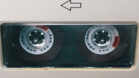 Audio Tape. Vintage Tape Recorder Plays Audio Cassette inserted therein. Macro static camera view of retro transparent audio cassette tape used for sound stock footage