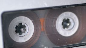 Audio Tape. Vintage Tape Recorder Plays Audio Cassette inserted therein. Macro static camera view of retro transparent audio cassette tape used for sound stock video footage