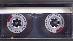 Audio Tape. Vintage Tape Recorder Plays Audio Cassette inserted therein. Macro static camera view of retro yellow audio cassette tape with a blank label used stock video footage
