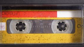 Audio Tape. Vintage Tape Recorder Plays Audio Cassette inserted therein. Macro static camera view of retro yellow audio cassette tape with a blank label used stock video