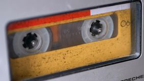 Audio Tape. Vintage Tape Recorder Plays Audio Cassette inserted therein. Macro static camera view of retro yellow audio cassette tape with a blank label used stock footage