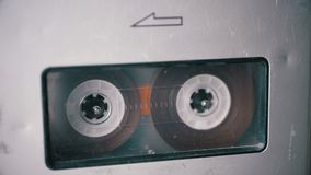 Audio Tape. Vintage Tape Recorder Plays Audio Cassette inserted therein. Macro static camera view of retro transparent audio cassette tape with a blank label stock footage