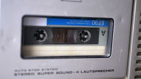 Audio Tape. Vintage Tape Recorder Plays Audio Cassette inserted therein. Macro static camera view of retro audio cassette tape with a blank label used for stock video footage