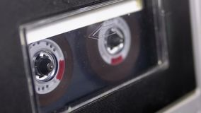 Audio Tape. Vintage Tape Recorder Plays Audio Cassette inserted therein. Macro static camera view of retro transparent audio cassette tape with a blank label stock video footage