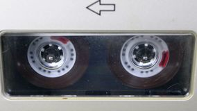 Audio Tape. Vintage Tape Recorder Plays Audio Cassette inserted therein. Macro static camera view of retro transparent audio cassette tape used for sound stock video