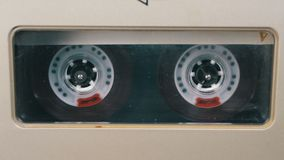 Audio Tape. Vintage Tape Recorder Plays Audio Cassette inserted therein. Macro static camera view of retro transparent audio cassette tape with a blank label stock video