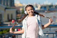 Audio tour headphones gadget. City guide and audio tour. Girl little tourist kid explore city using audio guide. Application. Free style of travelling. Exciting royalty free stock image