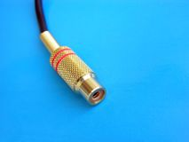 Audio Video Jack Macro. Macro of a gold-plated audio/video jack, over blue Royalty Free Stock Photography