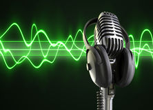 Audio Waves & Microphone. A microphone with headphones on top woth a audio wave background stock photo