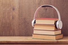 Audioboekenconcept met stapel oude boek en hoofdtelefoons op houten lijst Stock Foto