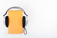 Audiobook στο άσπρο υπόβαθρο Τα ακουστικά βάζουν πέρα από το κίτρινο βιβλίο βιβλίων με σκληρό εξώφυλλο, κενή κάλυψη, διάστημα αντ Στοκ Φωτογραφία