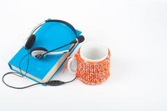 Audiobook на белой предпосылке Наушники положили над голубой книгой hardback, пустой крышкой, красной чашкой, космосом экземпляра Стоковые Изображения