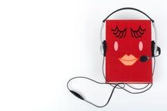 Audiobook на белой предпосылке Наушники положили над красной книгой hardback, пустой крышкой, космосом экземпляра для текста объя Стоковая Фотография RF