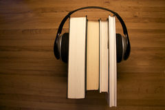 Audiobook. A set of headphones around a pile of books illustrating audiobooks royalty free stock image