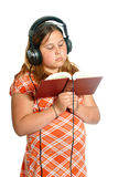 Audiobook. Concept image of a young girl listening to an audiobook, isolated against a white background Stock Photography