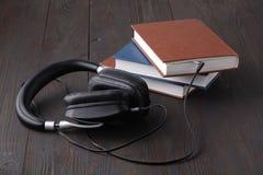 Audiobook begrepp med headphonen och den pappers- boken på tabellen Arkivfoto