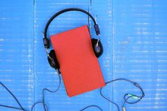 Audiobook concept. Book and headphones on wooden background Royalty Free Stock Photography