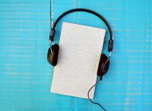 Audiobook concept. Book and headphones on wooden background Royalty Free Stock Image