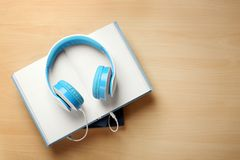 Audiobook concept. Open book with headphones stock photography
