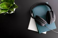 Audiobook concept with overhead shot of headphones on stack of books on black background stock photo