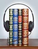 Audiobook with earphones. Audiobook with black earphones on shelf stock photography