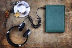 Audiobook hörlurar och bok på trätabellen Arkivfoton